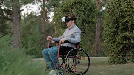 слепой : A disabled man in a wheelchair chair uses a virtual reality helmet Стоковые видеозаписи