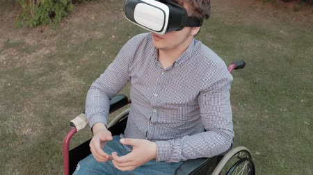 use laptop : A disabled man in a wheelchair chair uses a virtual reality helmet Stock Footage