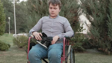 use laptop : A disabled man in a wheelchair chair removes the virtual reality helmet Stock Footage