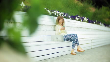 использование : Beautiful woman uses a smartphone on a wooden bench in the park