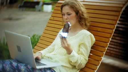босс : Beautiful woman eats an ice cream and works on a laptop on a wooden bench in the park
