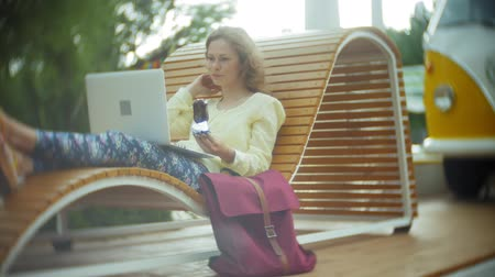 использование : Beautiful woman eats an ice cream and works on a laptop on a wooden bench in the park