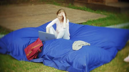 colaboração : Young woman uses a laptop, lying in a lounge area of the park on soft puffs