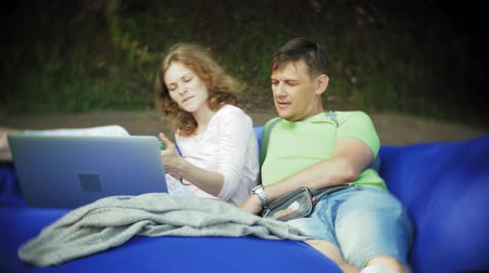 alliance : Young woman and mature man uses a laptop, lying in a lounge area of the park on soft puffs Stock Footage