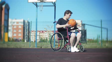 handikap : Disabled man plays basketball from his wheelchair, On open air
