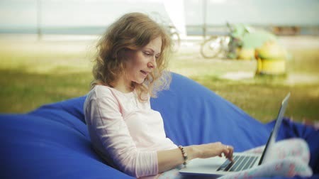 припадок безумия : Young woman uses a laptop, lying in a lounge area of the park on soft puffs