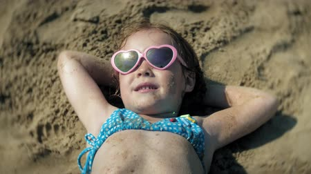 banhos de sol : baby girl sunbathing on the beach in sunglasses. close-up face Vídeos