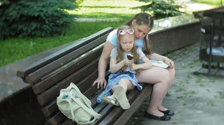 bank : Two little girls are sitting on a wooden bench in a city reading a book and eating ice cream, the background of a city park