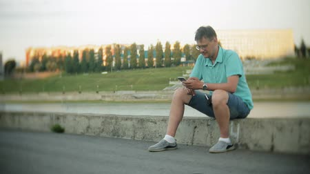 послать : Young happy man with a smartphone in the city park sits on the shore