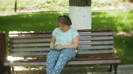 fat burning : Little fat girl with a tablet PC and headphones sitting on a bench listening to music or watching a video in a summer park