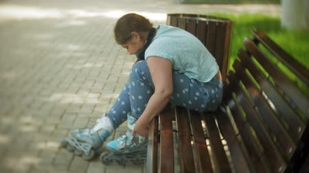 fat burning : Little fat girl sitting on a bench listening to music clothes roller skates in the park