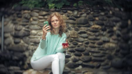 use computer : A woman is using a smartphone against a back wall. Drinks and drinks wine from a glass