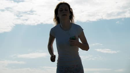 lélegzet : A young woman with a fine figure is engaged in gymnastics in the sea at dawn. She runs along the seacoast in headphones, Super slow motion