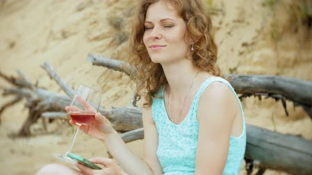 task : busy beautiful young woman working on a laptop computer with business papers picking up a phone to work a call sitting on the beach by the sea on a sunny day and drinking wine from a glass
