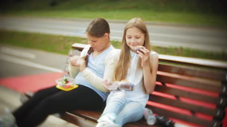 жевать : Two little girls, slim and fat, eat healthy and harmful food, vegetables and cakes sitting on a bench in a cafe, the concept of a healthy diet...