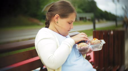 во : Close up of adorable little fat girl eating vegetables with her hands sitting on a bench in the park, concept of healthy eating Стоковые видеозаписи