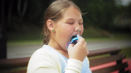 во : Close up of adorable little fat girl eating a cake with her hands sitting on a bench in the park
