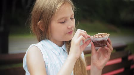 блаженство : Close up of adorable little girl eating a cake with her hands sitting on a bench in the park Стоковые видеозаписи