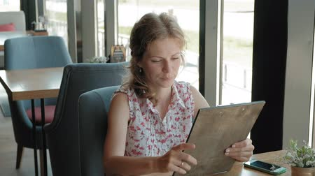 escolha : Woman is looking through the menu at the restaurant