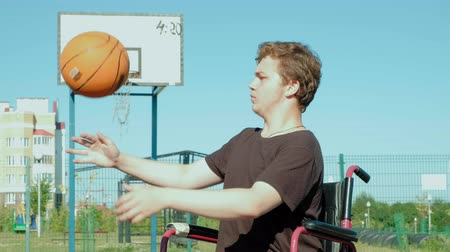 deficientes : Disabled man plays basketball from his wheelchair, On open air