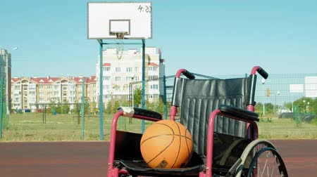 volleyball players : Type of wheelchair with a basket ball on a sports volleyball court