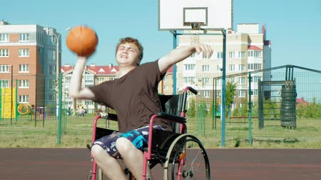 basketball : Disabled man plays basketball from his wheelchair, On open air, Make an effort when playing