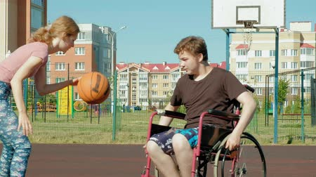 handikap : Disabled man plays basketball from his wheelchair With a woman, On open air, Make an effort when playing