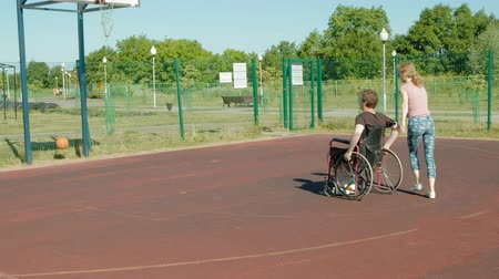 atirar : Disabled man plays basketball from his wheelchair With a woman, On open air, Make an effort when playing