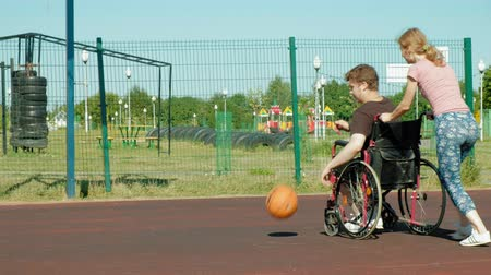 négy : Disabled man plays basketball from his wheelchair With a woman, On open air, Make an effort when playing