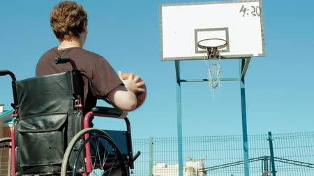 deficientes : Disabled man plays basketball from his wheelchair With a woman, On open air, Make an effort when playing