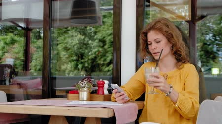 holding document : A beautiful young woman drinks a smoothie smoothie at a cafe