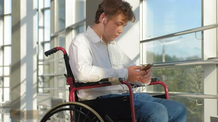 uses : disabled man on a wheelchair at a window listening to music on headphones from a smartphone