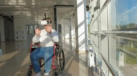 deficientes : disabled man on a wheelchair at a window uses a helmet of virtual reality