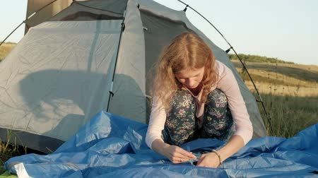 elszánt : Young woman collects a tourist tent near the old bridge