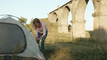 dedicado : Young woman collects a tourist tent near the old bridge