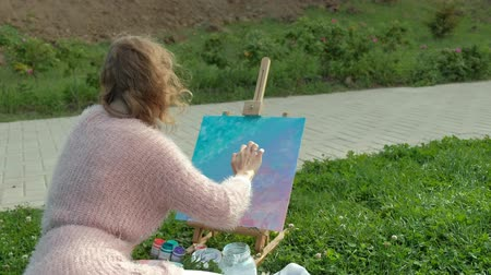 изображение : A pretty woman with red hair, paints a picture on canvas, which stands on the easel. The lady is in the open air near the lake of the river, she draws from life Стоковые видеозаписи