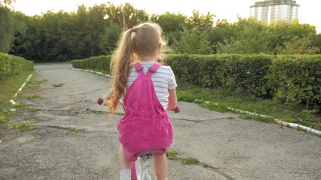 перемычка : A happy, beautiful, little girl with long blond hair in a pink skirt and jumper rides a childrens bike on the road, she smiles. Super slow motion