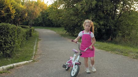 saltador : A happy, beautiful, little girl with long blond hair in a pink skirt and jumper rides a childrens bike on the road, she smiles. Super slow motion