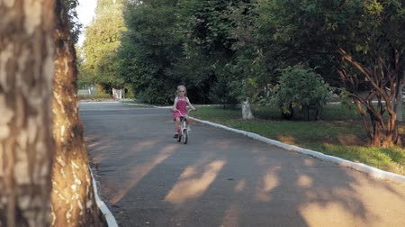 she : A happy, beautiful, little girl with long blond hair in a pink skirt and jumper rides a childrens bike on the road, she smiles. Super slow motion