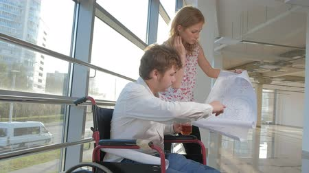 uses : disabled businessman on a wheelchair in a window with a picture on a large sheet of paper discussing work with a business woman, discussion in the office... Stock Footage