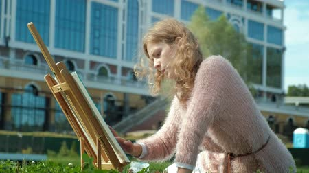 she : A pretty woman with red hair, paints a picture on canvas, which stands on the easel. The lady is in the open air near the lake of the river, she draws from life Stock Footage