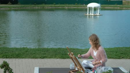 standlar : A pretty woman with red hair, paints a picture on canvas, which stands on the easel. The lady is in the open air near the lake of the river, she draws from life Stok Video