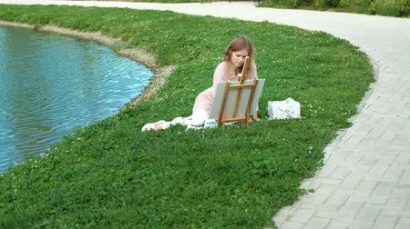 which : A pretty woman with red hair, paints a picture on canvas, which stands on the easel. The lady is in the open air near the lake of the river, she draws from life Stock Footage