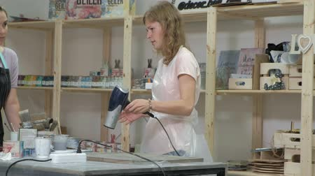 клетчатый : The woman in the workshop is working on wooden boards, creating an effect of antiquity