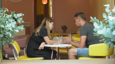 their : A business woman and a man at their break with their tablet sit in a cafe with yellow walls and discuss a project Stock Footage