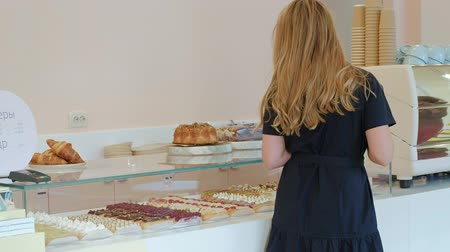 she : She buyer chooses yummy. Young attractive girl, woman buys in the coffee shop or pastries, cakes, cake, macaroon. A buyer standing under a a glass case at the bakery, coffee shop