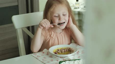 zabkása : Happy beautiful girl eating porridge for breakfast and having fun in white kitchen at home Stock mozgókép