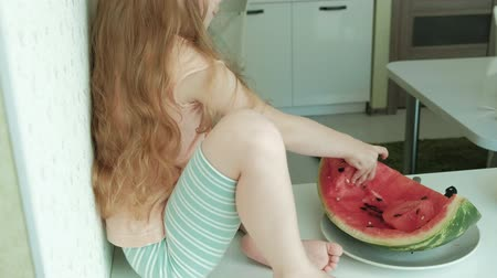 кусаться : Little girl eating a watermelon in the summer in the kitchen at home Стоковые видеозаписи