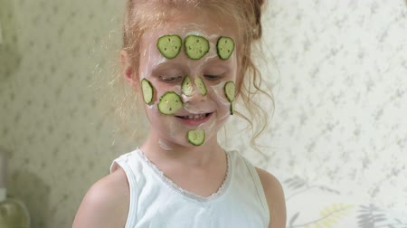 towel white : A woman with her daughter makes fun of cucumber masks at home