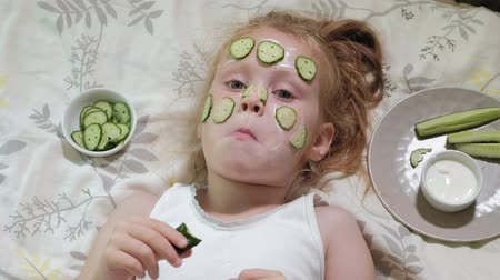 towel white : Little beautiful beautiful girl is making cucumber masks at home and eating vegetables